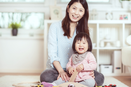 Pretty japanese woman playing with her cute laughing baby girl on the floor at home