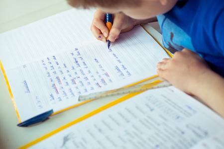 Intelligente jongen maakt huiswerk aan het bureau in zijn kamer Stockfoto