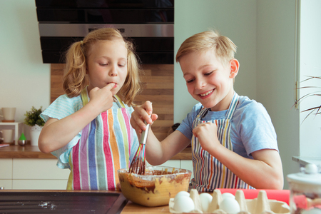 Two happy children having fun and taste chocolate dough in the modern kitchen during baking muffins Stock fotó