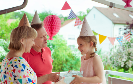 Portrait of happy grandparents celebrating birthday with their pretty little granddaughter on colorful decorated terrace Stock Photo
