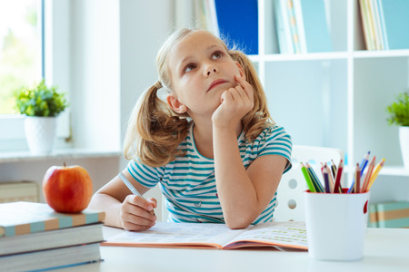 Portrait of a thoughtful cute girl sitting at a table with books and apple in a light class�ºroom
