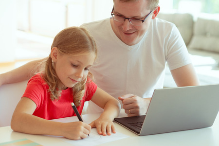 Happy young father have fun with his pretty little daughter during working with laptop at modern home