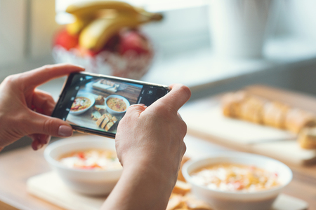 Primer plano de cómo las manos de la mujer tomando fotos de comida vegetariana en casa
