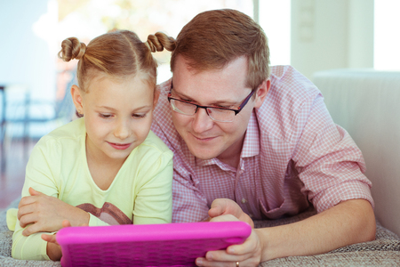 Happy young father have fun with his pretty little daughter during working with tablet at home on couch 스톡 콘텐츠