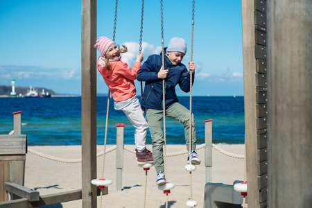 Two happy children playing at playground on a beach