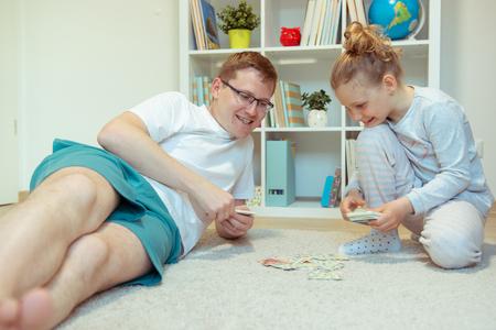 Glücklicher junger Vater, der mit seiner süßen kleinen Tochter im hellen Raum zu Hause spielt Standard-Bild