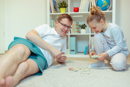 Szczęśliwy młody ojciec bawi się ze swoją uroczą córeczką w jasnym pokoju w domu Zdjęcie Seryjne