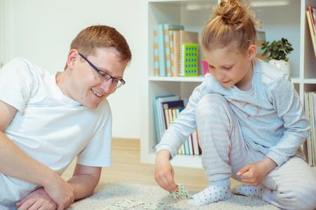 Glücklicher junger Vater, der mit seiner süßen kleinen Tochter im hellen Raum zu Hause spielt