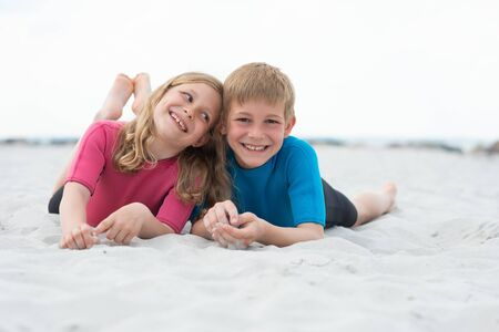 Portrait of two happy children in neoprene swimsuits playing on the beach with sand on Baltic sea Standard-Bild