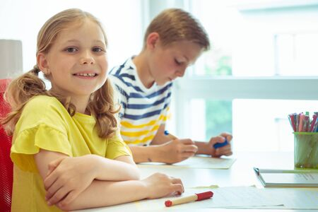 Cute schoolchildren are came back to school and learning and writing  at the table in classroom
