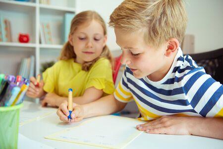 Süße Schulkinder sind zurück in die Schule gekommen und lernen und schreiben am Tisch im Klassenzimmer
