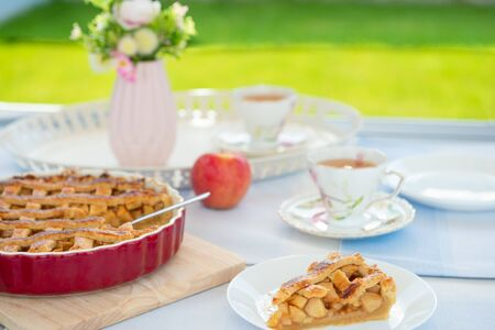 Fresh baked apple pie, cup of tea and flowers on a table at home on cozy terrace