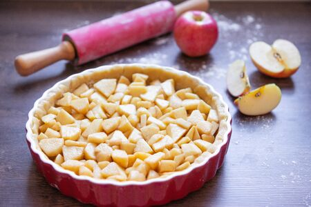 Traditional homemade apple pie and ingredients such as apple and cinnamon on wooden background for autumn holiday