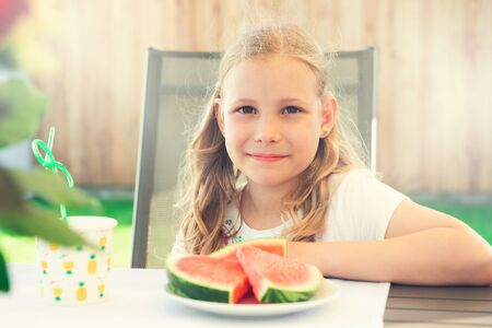 Portrait of happy cute little girl eating sweet red watermelonin garden at home