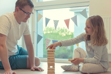 Young happy father playing with his cute daughter with wooden blocks at home