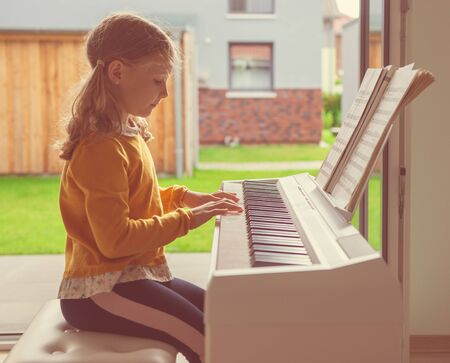 Portrait of pretty little girl having piano lesson at modern white e-piano at home