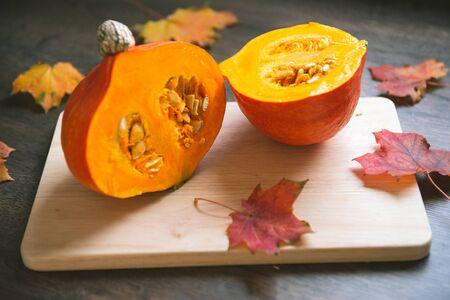 Closeup photo of sliced hokkaido pumpkin on cutting board with colorful leaves  Stock Photo