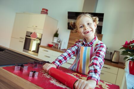 Pretty little girl with funny pigtails decoraiting christmas cookies of different forms in modern kitchen