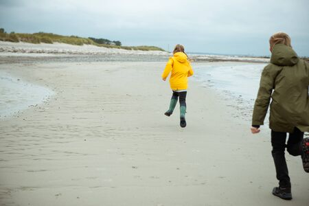 Two happy children running and jumping on water of Baltic sea in rubber boots at windy and cold weather
