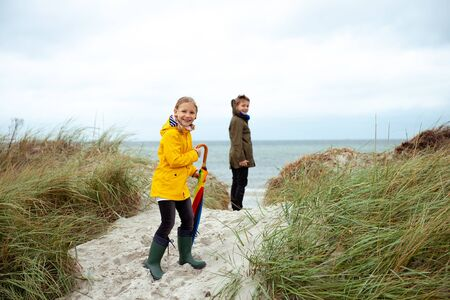 Two happy teenager siblings staing with ambrella on coast of Baltic sea at windy rainy weather