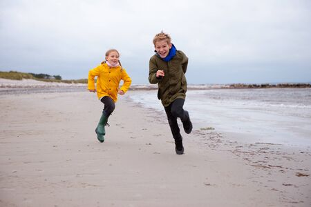 Two happy children running and jumping on water of Baltic sea in rubber boots at windy and cold weather Stockfoto - 133317143