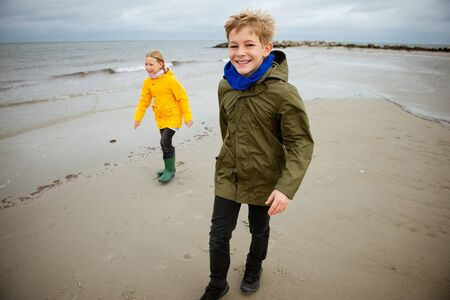 Two happy children running and jumping on water of Baltic sea in rubber boots at windy and cold weather Stockfoto - 133316848