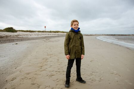 Portrait of handsome teenager staing on coast of Baltic sea with lighthouse on background Standard-Bild