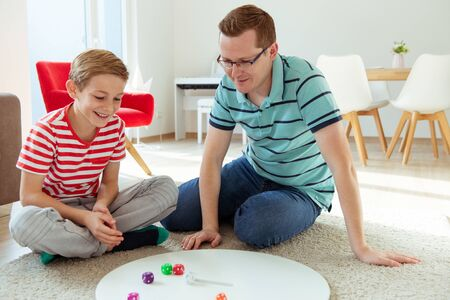 Happy young father plays with his teenager son Board Game with colorful dices at home