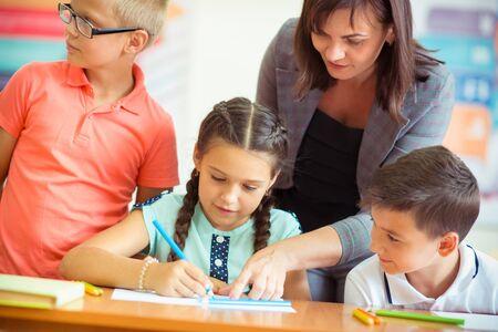Yong bella insegnante con un gruppo di bambini clewer a scuola a klassroom