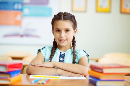 Portrait of pretty schoolgirl sitting at desk with many colorful books in classroom