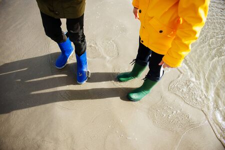 Two children standing im water of cold Baltic sea in colorful rubber high boots