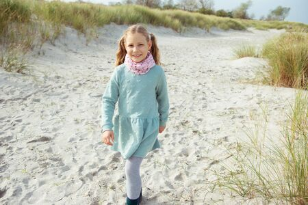 Portrait of pretty cheerful little girl in dress at sunny day on beach of  Baltic sea