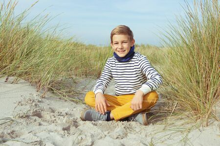 Portrait of handsome teenager boy sitting on white sand on beach of Baltic sea at sunny day 免版税图像