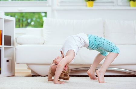 Cute little child girl making morning exercises and yoga at home Archivio Fotografico
