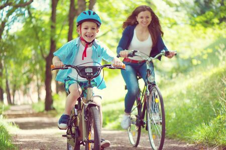 Happy young mother and her little son ride on bikes in summer park
