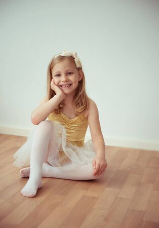 Cute little blonde girl sitting in ballet tutu with a bow in her hair