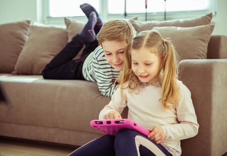 Teen brother and sister working with tablet at home during coronavirus quarantine Stock Photo