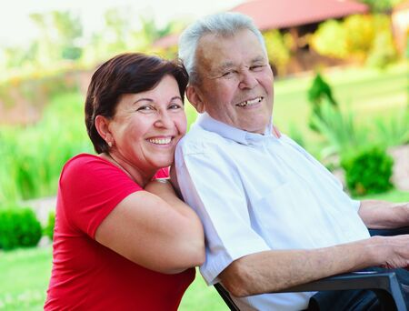Portrait of happy old father and his 50 years daughter at nurising home