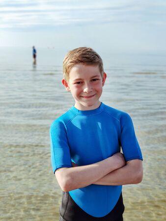 Portrait of handsome teen boy in neoprene swimsuit in Baltic sea Reklamní fotografie