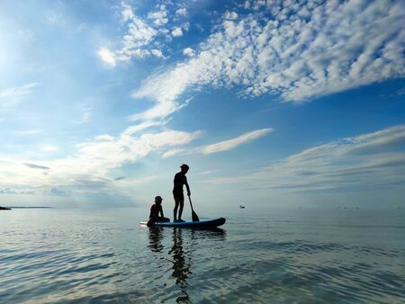 Happy teenager children in neoprene suits  having fun on SUP board and  paddling in Baltic sea