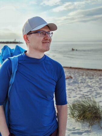 Portrait of handsome young man standing with SUP board on beach with white sand at Baltic sea