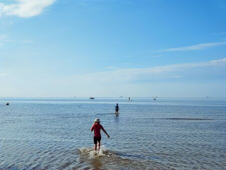 Two happy siblings children in neoprene swimingsuit  playin and running in Baltic sea