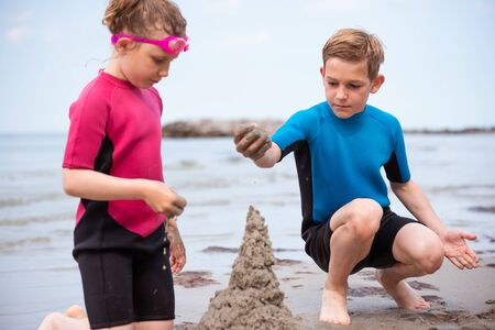 Two happy siblings children in neoprene swimsuits playing with sand in a Baltic sea