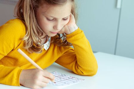 Portrait of dorable but tired teen girl solving sudoku at desk at school or at home. View from above