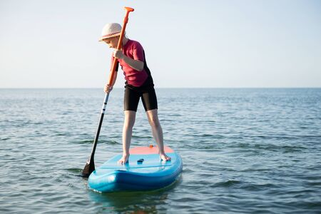 Happy teen child girl paddling on sup board in Baltic sea