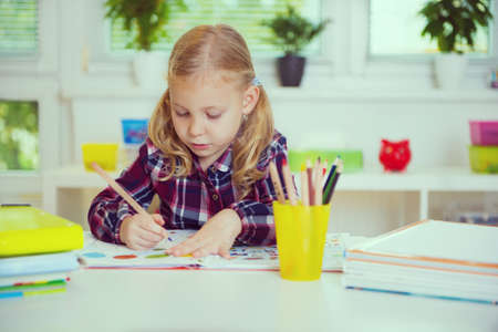 Portrait of pretty school girl in yellow are studying at classroom at the table Stock Photo