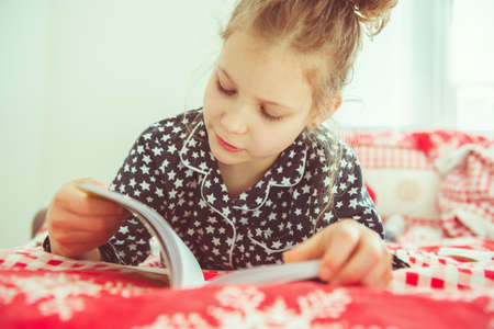 Adorable little child girl reading book having quarantine because of coronavirus Фото со стока