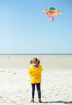 Cheerful little girl running in dress on beach with kite at sunny day