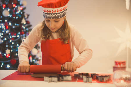 Pretty little girl decoraiting christmas cookies of different forms at home with christmas tree on background Standard-Bild