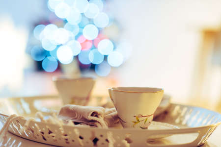 Cozy closeup photo of cups of tea on tray with christmas tree on background Фото со стока